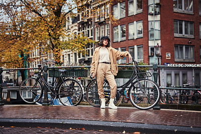 Buy stock photo Shot of a beautiful young woman touring the city with a bicycle