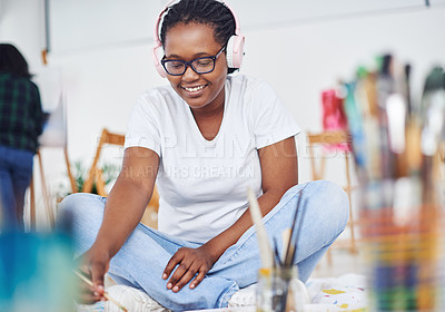 Buy stock photo Shot of a young woman wearing headphones while painting in a art studio