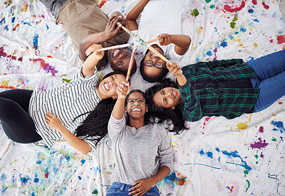 Buy stock photo Shot of a group of artists holding their paint brushes together
