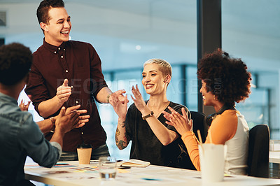 Buy stock photo Cropped shot of a group of young businesspeople applauding a colleague during a meeting in their office