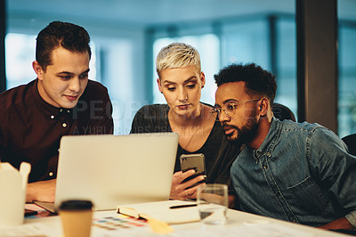 Buy stock photo Cropped shot of three young businesspeople working together in their office