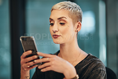Buy stock photo Cropped shot of an attractive young businesswoman using her cellphone while working in the office