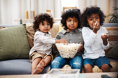 Buy stock photo Cropped shot of three adorable little boys eating popcorn and watching movies together at home