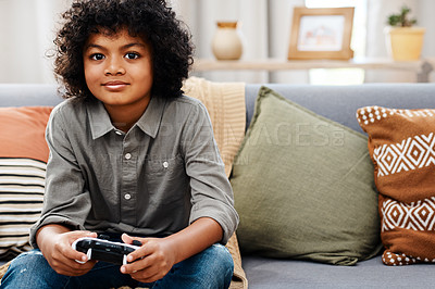 Buy stock photo Cropped shot of an adorable little boy sitting on a sofa and playing video games at home