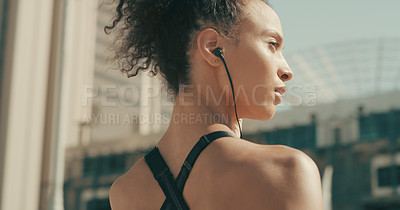 Buy stock photo Rearview shot of a sporty young woman listening to music while exercising in the city