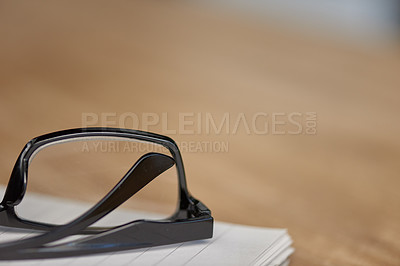 Buy stock photo Still life shot of a pair of glasses and a note pad on a wooden table