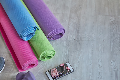 Buy stock photo High angel shot of yoga mats and a cellphone on a wooden surface