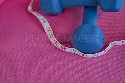 Buy stock photo High angle shot of a dumbbells and a measuring tape against a pick background