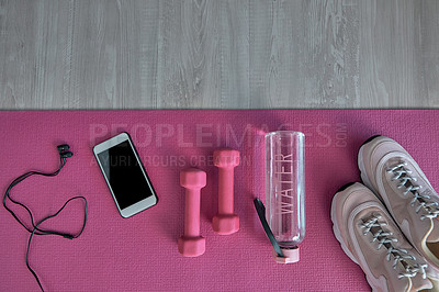 Buy stock photo High angle shot of a variety of workout equipment laid out on a pink exercise mat before a workout