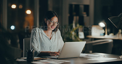 Buy stock photo Cropped shot of an attractive young businesswoman sitting alone and using her laptop during a late night in the office