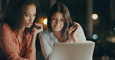 Buy stock photo Cropped shot of two young businesswomen sitting together in the office and using a laptop during a late shift