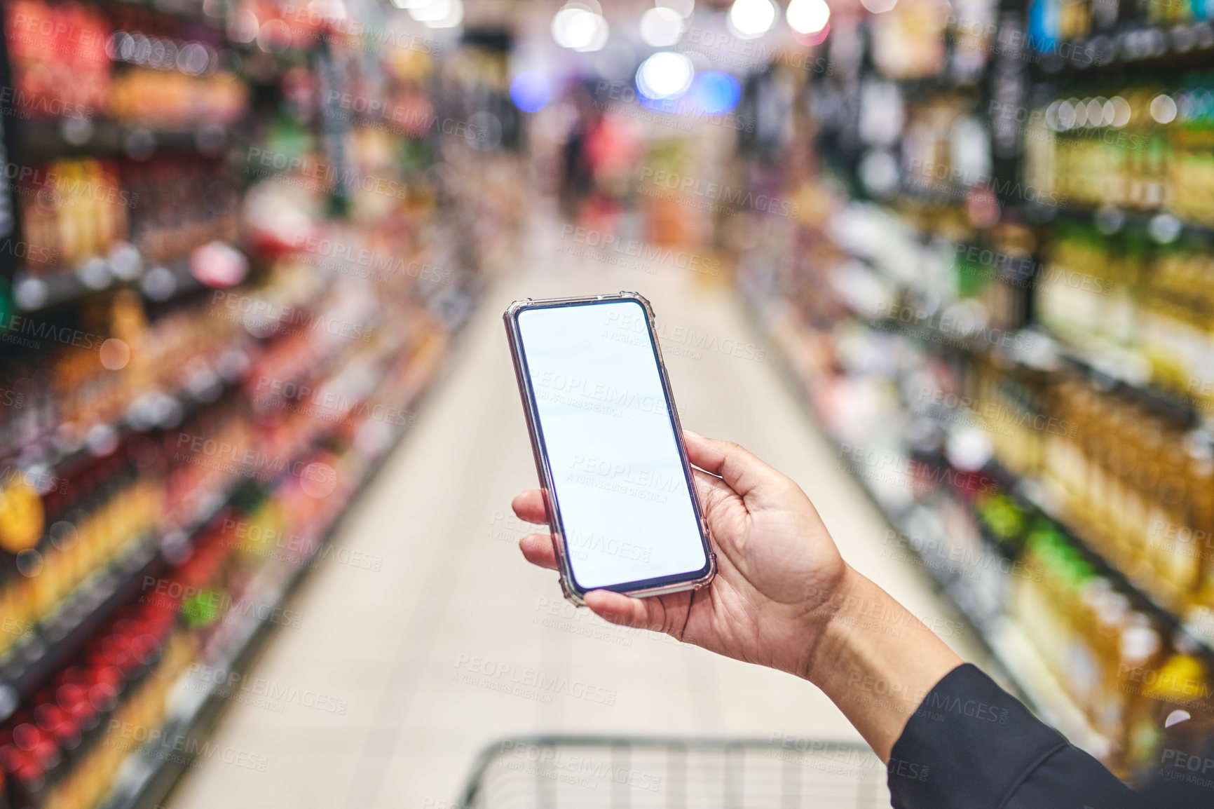 Buy stock photo Cropped shot of a woman using a smartphone while shopping in a grocery store