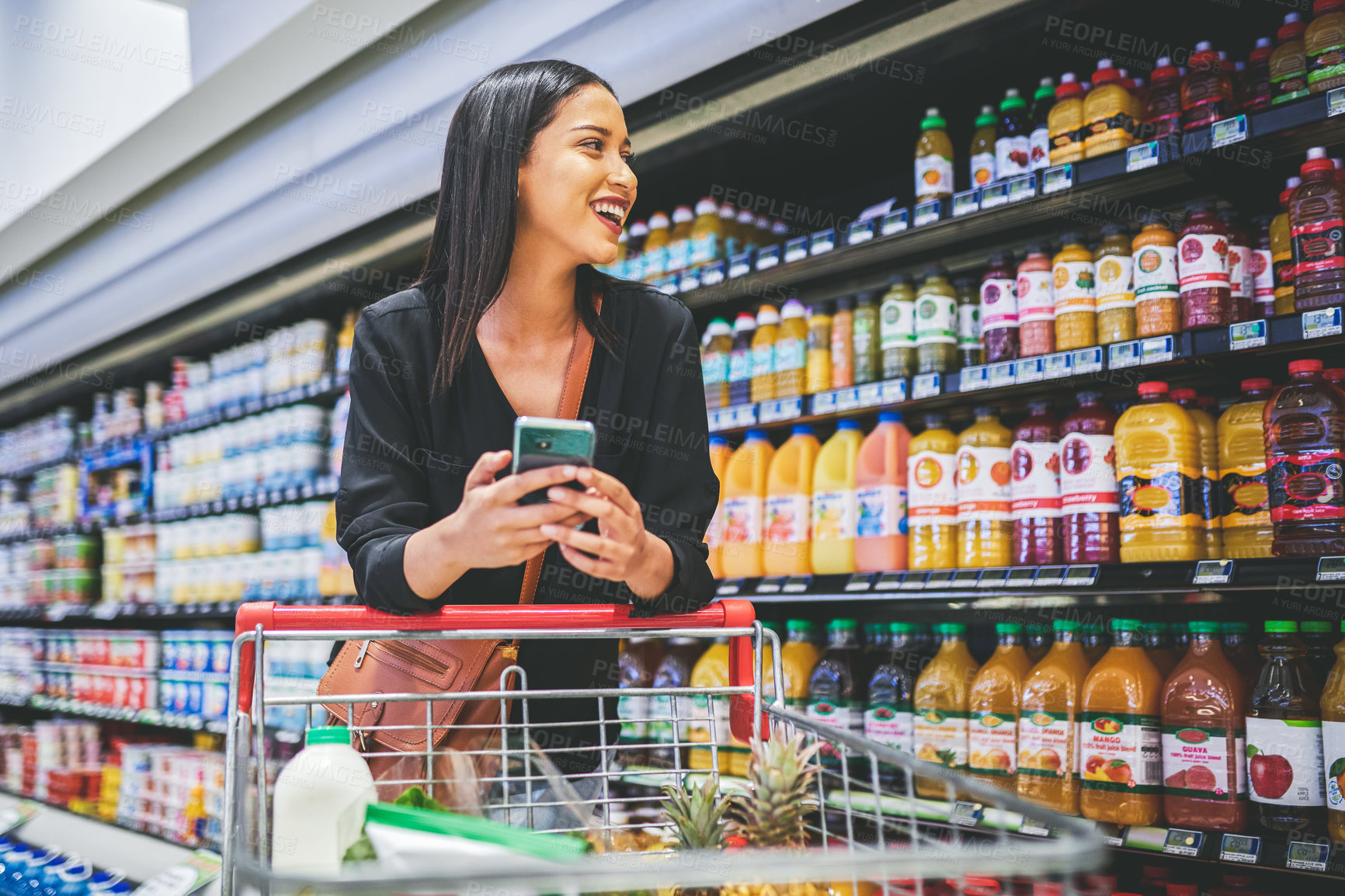 Buy stock photo Shot of a young woman using a smartphone while shopping in a grocery store