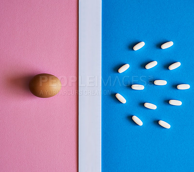 Buy stock photo Studio shot of an egg placed adjacent to a bunch of pills against a mixed background