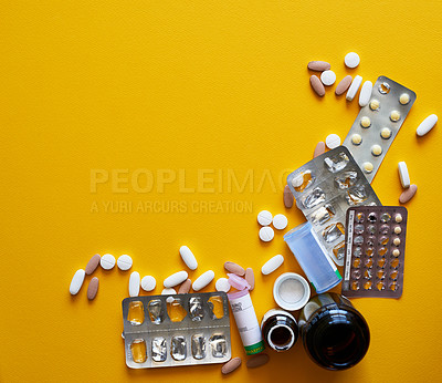 Buy stock photo Studio shot of a bunch of tablets and pill blister packs against a mustard background