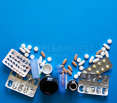 Buy stock photo Studio shot of a bunch of tablets and pill blister packs against a blue background