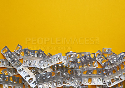 Buy stock photo Studio shot of a bunch of  empty blister packs against a mustard background
