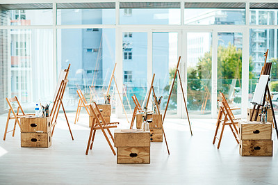 Buy stock photo Cropped shot of a group of easels and canvases in an empty art studio before a painting class