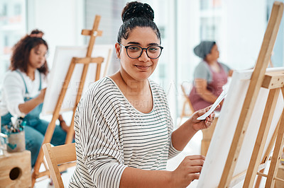 Buy stock photo Cropped portrait of an attractive young woman sitting with her friends and painting during an art class in the studio