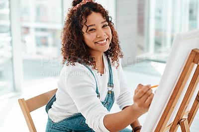 Buy stock photo Cropped portrait of an attractive young artist sitting alone and painting during an art class in the studio