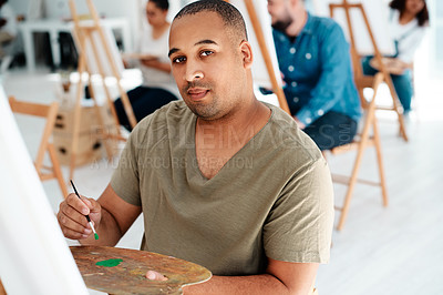 Buy stock photo Cropped portrait of a handsome young artist holding a palette during an art class in the studio