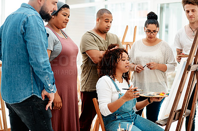 Buy stock photo Cropped shot of an attractive young woman sitting and explaining her artwork to her friends during an art class