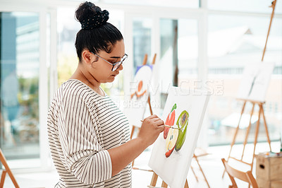 Buy stock photo Cropped shot of an attractive young artist standing alone and painting during an art class in the studio