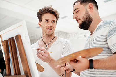 Buy stock photo Cropped shot of a handsome young man standing with his friend and painting during an art class in the studio
