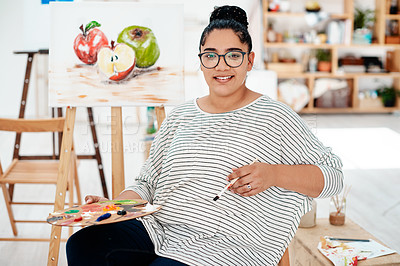 Buy stock photo Cropped portrait of an attractive young artist sitting alone in the studio and holding a palette during an art class