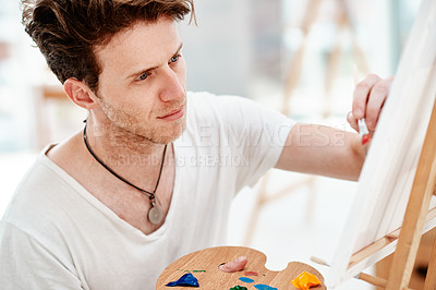 Buy stock photo Cropped shot of a handsome young artist sitting alone and painting during an art class in the studio
