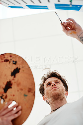 Buy stock photo Low angle shot of a handsome young artist standing alone and painting during an art class in the studio