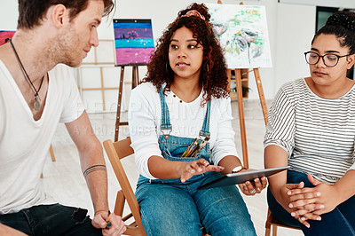 Buy stock photo Cropped shot of a diverse group of friends sitting together and using a tablet during an art class