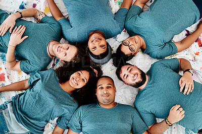 Buy stock photo High angle portrait of a diverse group of friends lying down in a circle during an art class