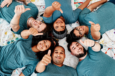 Buy stock photo Cropped portrait of a diverse group of friends lying down and showing a thumbs up after an art class