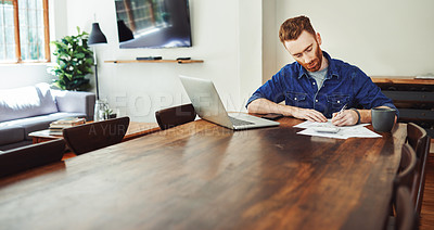 Buy stock photo Shot of a young man using a laptop while going through paperwork at home