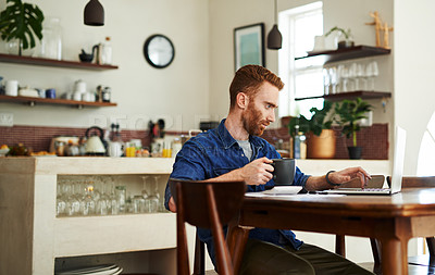 Buy stock photo Shot of a young man drinking coffee while using a laptop and going through paperwork at home