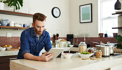 Buy stock photo Shot of a young man using a digital tablet while having breakfast in the kitchen at home