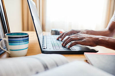 Buy stock photo Cropped shot of an unrecognizable man working on his laptop while studying at home during the day