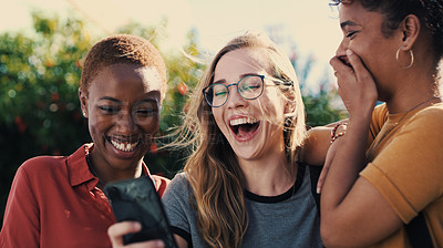 Buy stock photo Cropped shot of a diverse group of female friends using a cellphone while sightseeing in the city