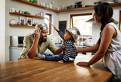 Buy stock photo Shot of an adorable young family having fun with pots and pans in the kitchen