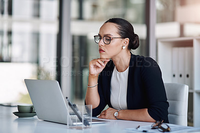 Buy stock photo Cropped shot of an attractive young businesswoman working on a laptop inside her office