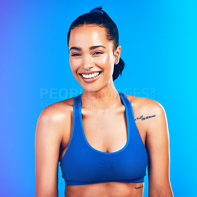 Buy stock photo Studio portrait of an attractive young sportswoman posing against a blue background