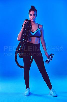 Buy stock photo Full length shot of an attractive young sportswoman posing carrying battle ropes against a blue background