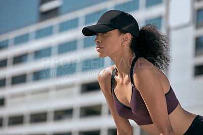 Buy stock photo Shot of a sporty young woman exercising in the city