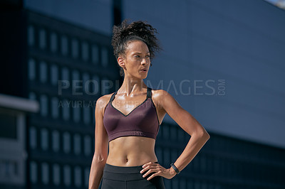 Buy stock photo Shot of a sporty young woman looking thoughtful while exercising in the city