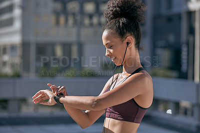 Buy stock photo Shot of a sporty young woman checking her watch while exercising in the city