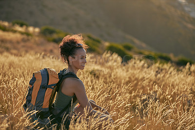 Buy stock photo Shot of an attractive young woman taking a break while hiking out in the mountains on a sunny day