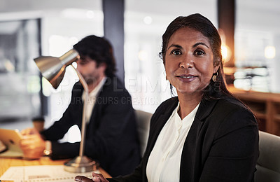 Buy stock photo Portrait of a confident mature businesswoman working late at night in a modern office