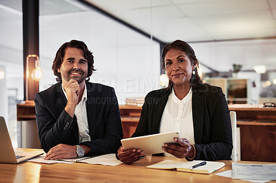 Buy stock photo Shot of a businessman and businesswoman using a digital tablet during a late night meeting in a modern office