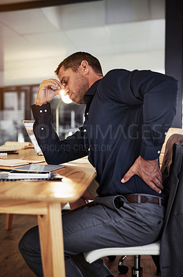 Buy stock photo Shot of a mature businessman experiencing back pain during a late night in a modern office